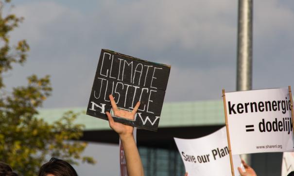 Собравшиеся у офиса издания люди выражали недовольство освещением в СМИ климатических изменений.