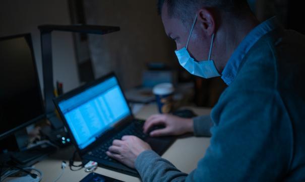 Мужчина работает за ноутбуком в защитной медицинской маске