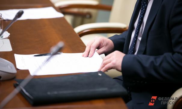 Человек в костюме с бумагами в руках