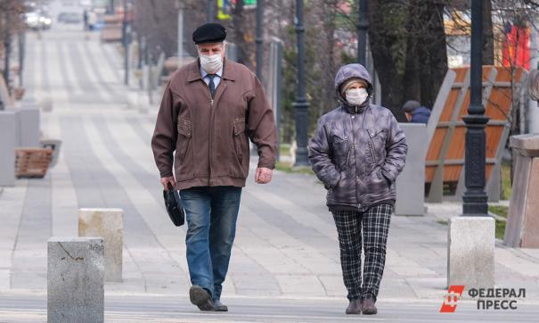 Пожилые люди в масках идут по городу