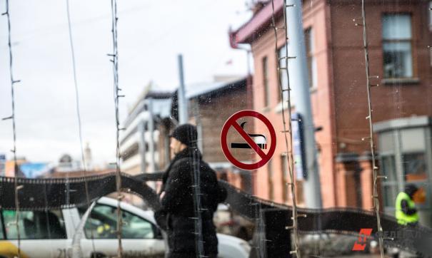 Прохожий и запрещающий курение знак