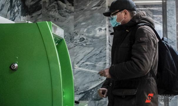 Мужчина снимает деньги в банкомате