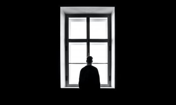 Мужчина смотрит в окно