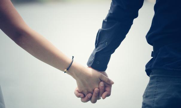 Молодые люди держатся за руки